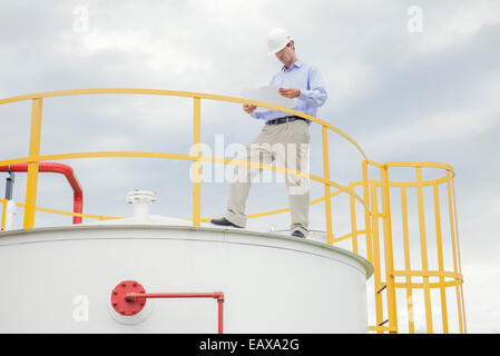 Engineer reviewing plans at industrial plant - Stock Photo