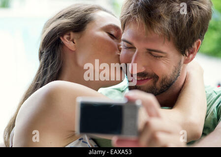 Couple kissing and taking selfie - Stock Photo
