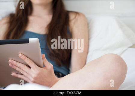 Woman using digital tablet in bed - Stock Photo