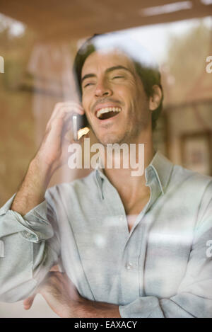 Man using cell phone bursting out laughing - Stock Photo