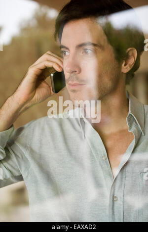 Man using cell phone looking out window - Stock Photo