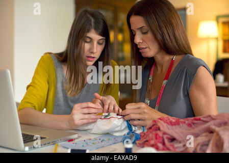 Mother and daughter doing embroidery together - Stock Photo