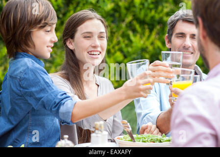 Family clinking glasses at outdoor gathering - Stock Photo