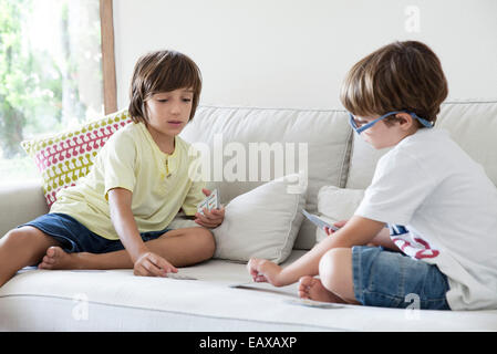 Boys sitting on sofa playing cards - Stock Photo