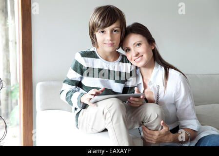 Mother and son sitting together on sofa with digital tablet - Stock Photo