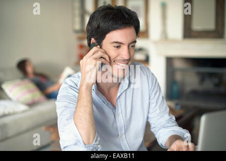 Man talking on cell phone while using laptop computer - Stock Photo