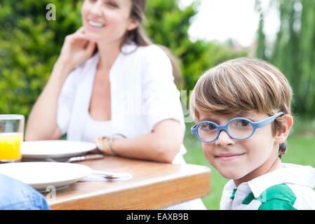 Little boy sitting at outdoor table with family, smiling at camera - Stock Photo