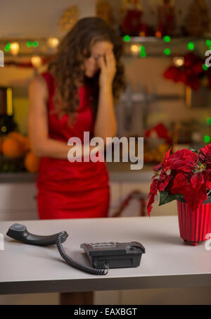 Closeup on phone and stressed young housewife in background - Stock Photo