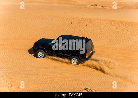 A four-wheel drive jeep driving over sand dunes in the desert of Oman. - Stock Photo