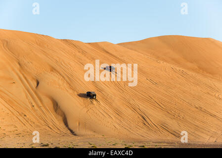 Two four-wheel drive jeep driving over sand dunes in the desert of Oman. - Stock Photo