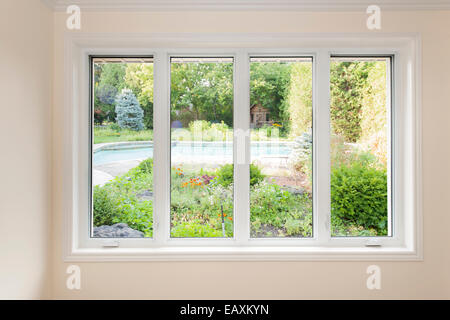Large four pane window looking on summer backyard with pool and garden - Stock Photo