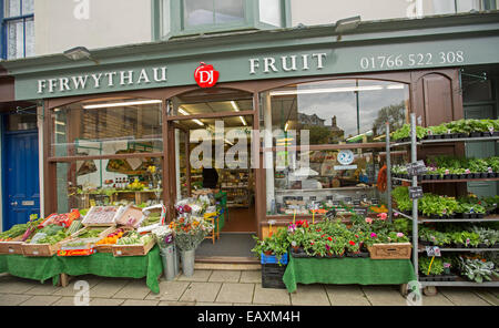 Fruit shop in Criccieth, Wales with signs in both English & Welsh, boxes of fruit on sale on footpath stall & customer - Stock Photo