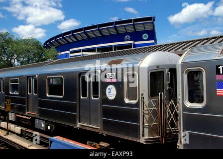 Queens, New York:  #7 Flushing line subway train stopped at the Shea Stadium station and old Shea Stadium - Stock Photo