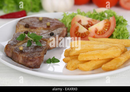 Pork chop steak cutlet meat meal with fries, vegetables and lettuce on plate - Stock Photo