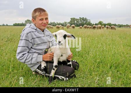 DJURDJENOVAC, CROATIA - JULY 25 : A young shepherd holding a baby goat on a meadow on July 25th, 2010 in Djurdjenovac, - Stock Photo