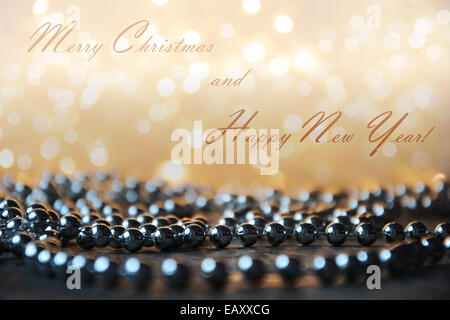 Yellow Christmas lights background with silver pearls on wooden floor and text effect - Stock Photo