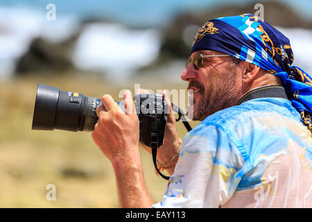 Male photographer with DSLR camera ready for action on the beach - Stock Photo