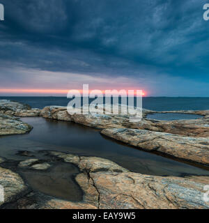 Rocky coast with dramatic sky during sunset - Stock Photo