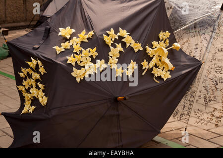 Black umbrella decorated with yellow paper flowers and umbrellas in Admiralty, Hong Kong - Stock Photo