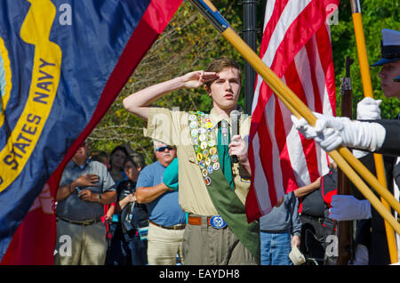 An Eagle Scout delivers the Pledge of Allegiance as a Color Guard presents the American, Navy and Marine Flags - Stock Photo