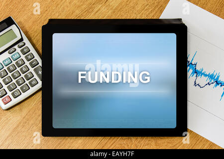 funding word on digital tablet with calculator and financial graph - Stock Photo