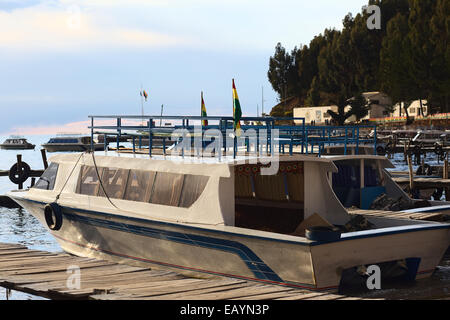 Motorboats docked at wooden jetty in the harbor on the shore of Lake Titicaca in Copacabana, Bolivia - Stock Photo