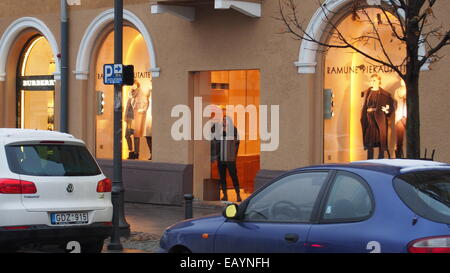 Vilnius,Lithuania. Young woman looking through the glass door of Haute couture shop. - Stock Photo