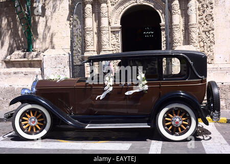 Vintage Buick car decorated with flowers for a wedding standing in front of the church of Yanahuara, Arequipa, Peru - Stock Photo