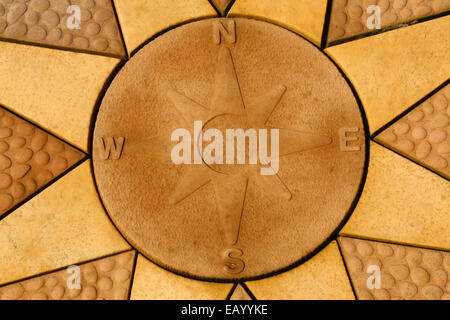 Stone compass rose set within a star. Golden coloured paving slabs. - Stock Photo