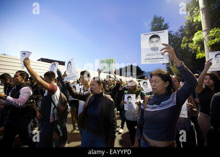Caravan for Ayotzinapa and demonstrators hold posters and placards during a march for the disappearance of 43 students - Stock Photo