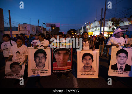 Parents and relatives of the 43 missing students from Ayotzinapa's teacher training college hold images of the missing - Stock Photo