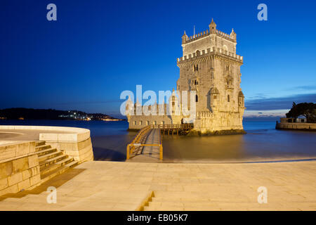 Belem Tower at night in Lisbon, Portugal, promenade along Tagus River. - Stock Photo