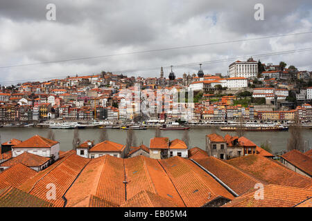 City of Porto in Portugal, view over wine cellars rooftops towards historic city centre along Douro river. - Stock Photo