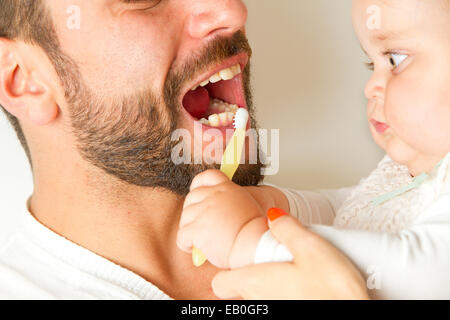 Baby brushing teeth of father - Stock Photo