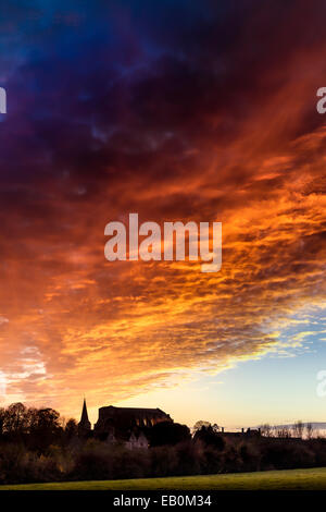 Malmesbury, Wiltshire, UK. 23rd November 2014. The sky turns orange as the sun sets over the Abbey in the Wiltshire - Stock Photo