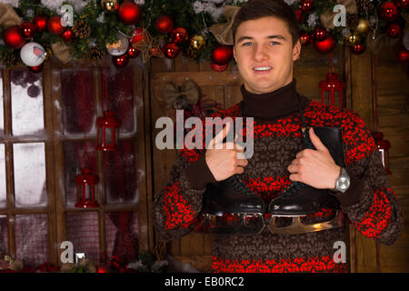 Close up Handsome Young Man in Winter Outfit Holding a Pair of Ice Skates in Front Christmas Decors on the Wall, - Stock Photo