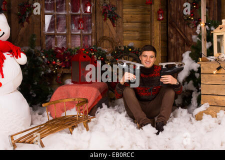 Young Handsome Man Sitting on the Floor with Cotton Snow in Winter Showing Ice Skates Surrounded by Beautiful Christmas - Stock Photo