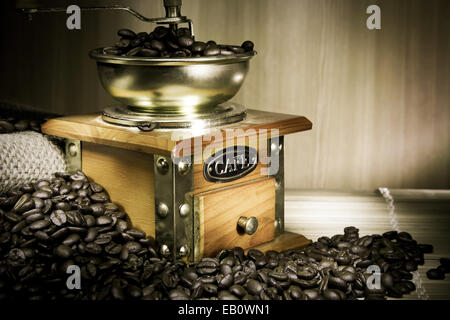 coffee grinder, beans and sacking on wood in night - Stock Photo