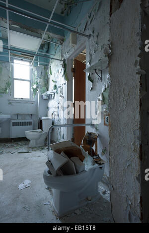 A patient shared washroom in an abandoned hospital with peeling paint on the walls. Ontario, Canada. - Stock Photo