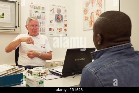 Hamburg, Germany. 06th Nov, 2014. Volunteering physician Detlev Nieburh (L) from Malteser-Migranten-Medizin (Maltese - Stock Photo