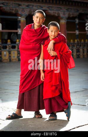 Young Bhutanese Buddhist monks in crimson robes at Paro Dzong, Bhutan - Stock Photo