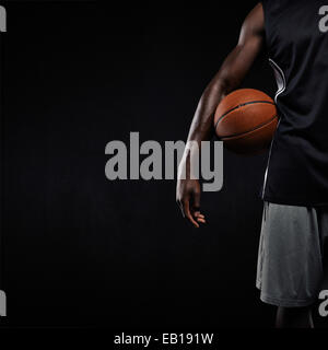 Cropped image of black basketball player standing with a basket ball. Man in sportswear holding basketball with - Stock Photo
