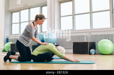 Female trainer helping senior woman to bend over. Old woman doing yoga on a exercise mat with physical therapist - Stock Photo