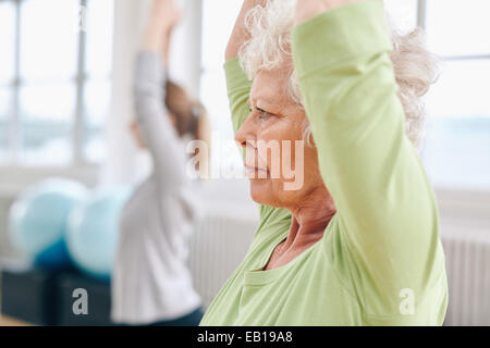 Close-up image of senior woman practicing yoga at gym. Active senior woman exercising at health club with female - Stock Photo