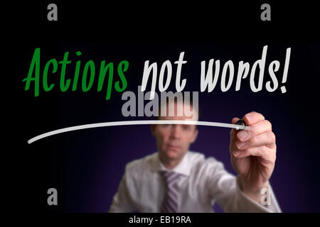 A businessman writing Actions not Words on a screen. Business Concept. - Stock Photo