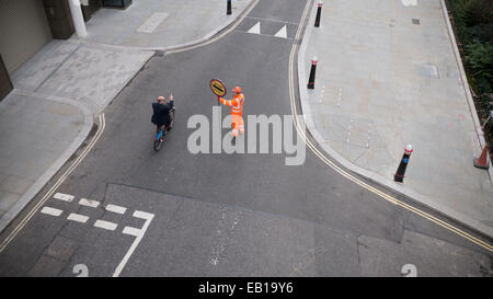 Asking directions from Banksman traffic marshall with fluorescent suit and helmet with stop works sign directing - Stock Photo