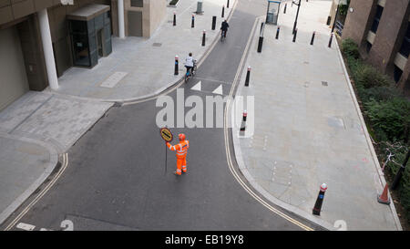 Banksman traffic marshall  with fluorescent suit and helmet with stop works sign directing Boris bikes in London - Stock Photo