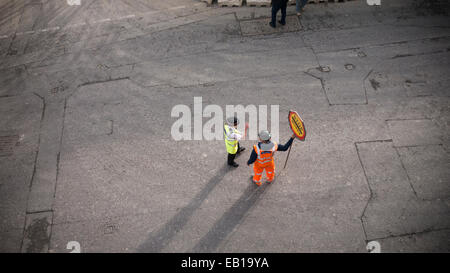 Banksman traffic marshall  with fluorescent suit and helmet with stop works sign talking to female police officer - Stock Photo