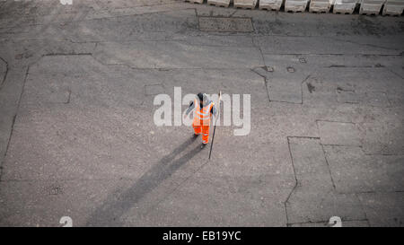 Banksman traffic marshall with fluorescent suit and helmet with stop works sign directing traffic London - Stock Photo