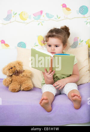 kid girl reading story for teddy bear - Stock Photo